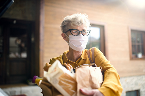 Senior woman wearing face mask who is receiving bagged groceries