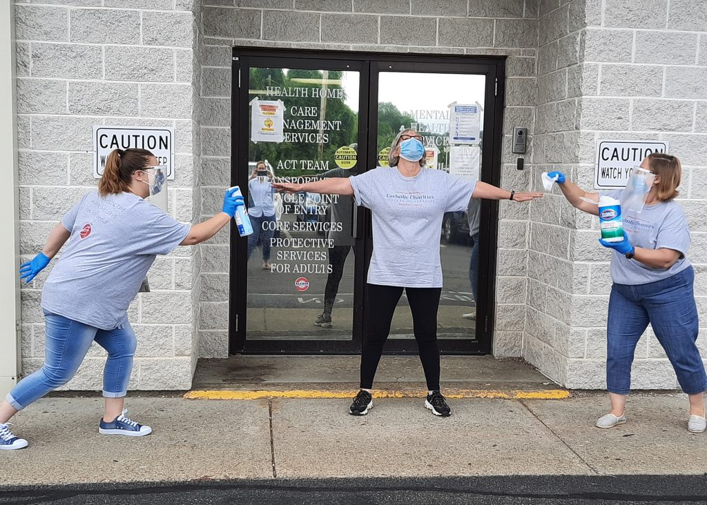 Staff posing outside Catholic Charities with masks and cleaning supplies