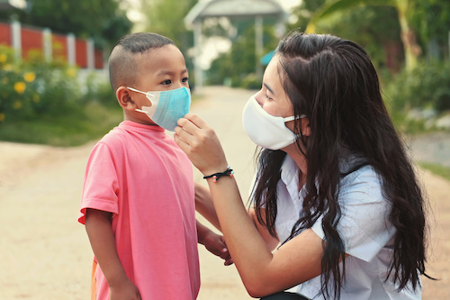 Mother helping child put on face mask to protect from COVID-19